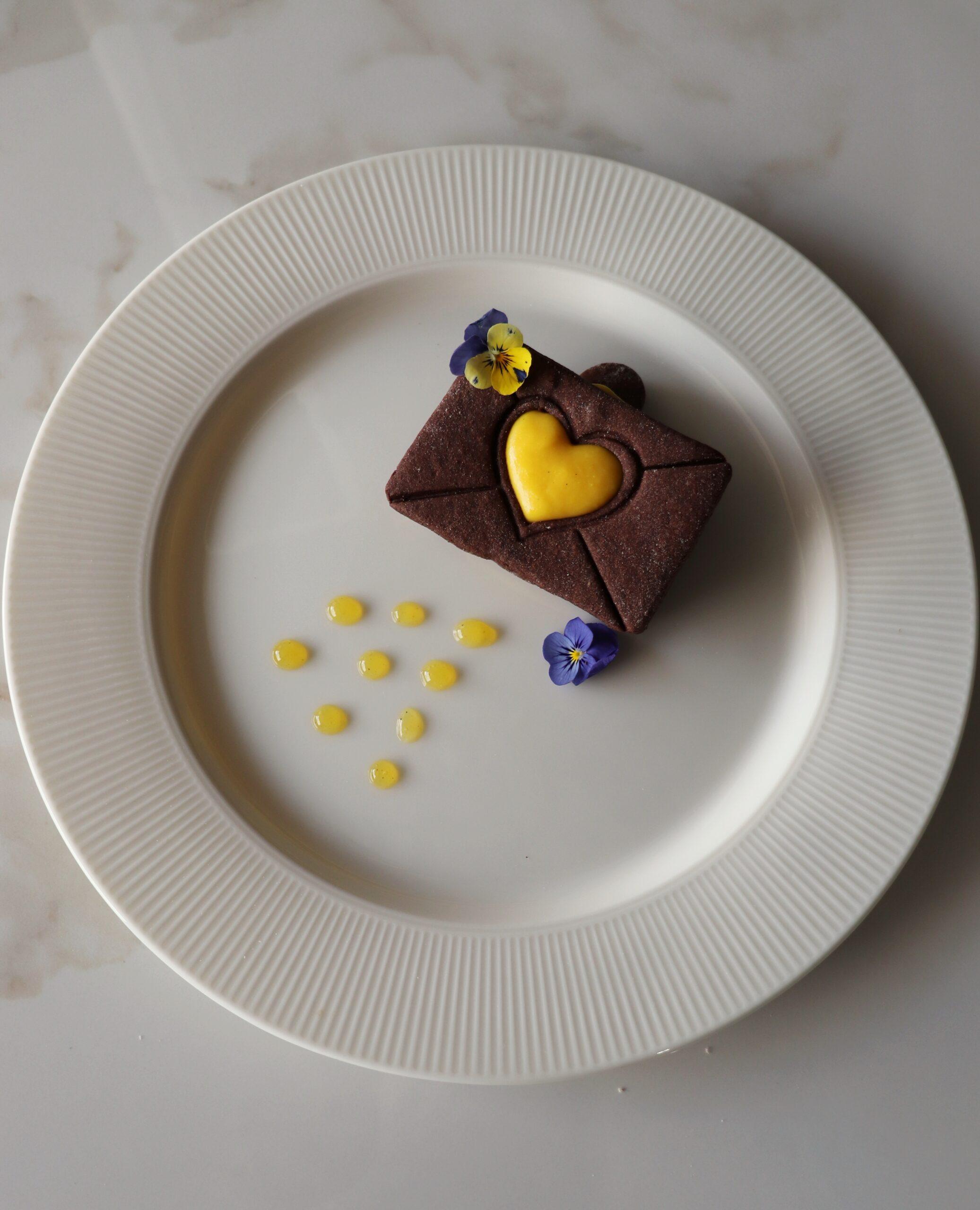 Biscotto al cacao con crema allo zafferano e riduzione di arancia